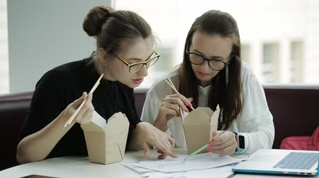 Çin yemek çubukları : Two beautiful women with glasses eating chopsticks noodles out of boxes while working on an urgent business project