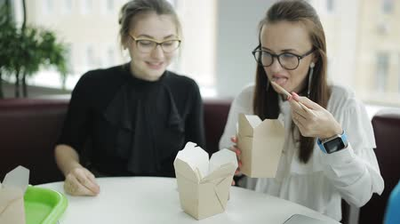 kínai evőpálcikák : Two beautiful women with glasses eating chopsticks noodles out of boxes while working on an urgent business project