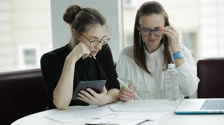 стулья : Two business woman working with documents, a laptop and a tablet sitting at the table. Business meeting two companions and discuss all the fields of future business.