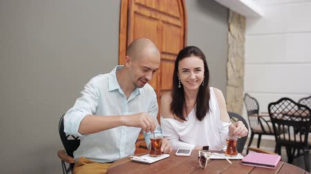 ilgi yeri : man and woman drinking tea and talking in a cozy cafe Stok Video
