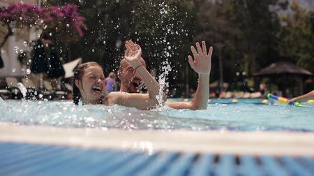 волнение : Young dad with a daughter playing and splashing in the pool