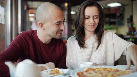 кусаться : A married couple eating pizza at a pizzeria during lunchtime Стоковые видеозаписи