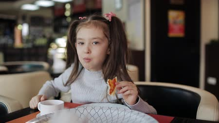 calabresa : Happy girl in pink wear eats appetizing pizza in pizzeria Stock Footage