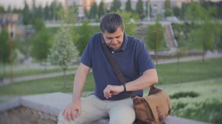 pedometer : A tired middle-aged man sat down to rest after climbing stairs. A man checks on a smartphone the number of steps. Stock Footage