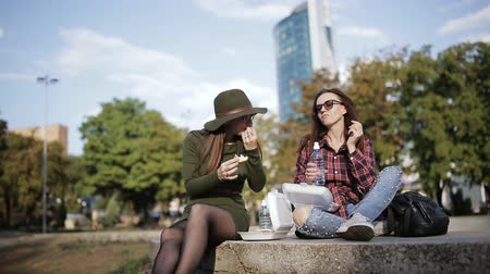 fries : Two different and unusual women eat on the street sandwiches and fries. Stock Footage