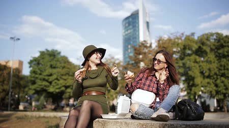 tüketmek : Two different and unusual women eat on the street sandwiches and fries. Stok Video