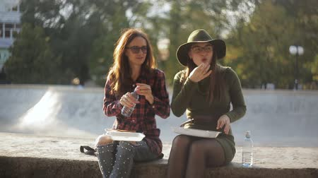 tüketmek : Two girls hipster in a city Park to eat sandwiches, drink water and communicate Stok Video