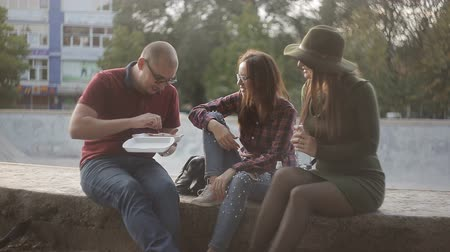group people : Friends eat in the street, laughing and relaxed talk