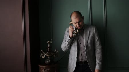 dizgi : Handsome man businessman in suit talking on an old vintage phone