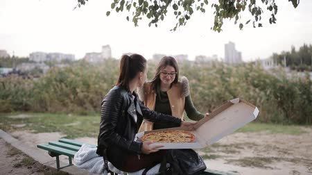cheese slices : Two women eating pizza in a large box in the city sitting on a bench on the promenade