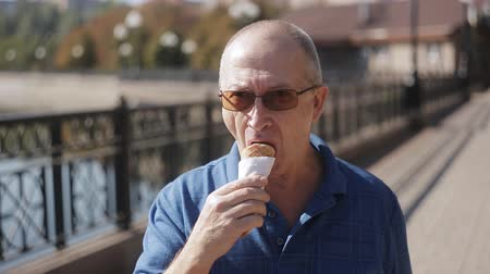 oplatka : Portrait of Elderly man eating ice cream in a waffle cone in front of the camera