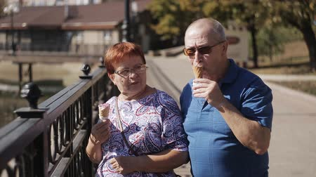 consumir : Elderly married couple walking along the promenade with ice cream and talk