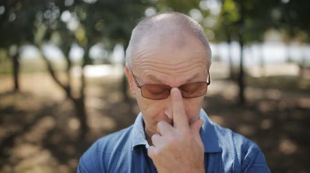 milestone : Portrait of elderly man with glasses in the Park looking at the camera