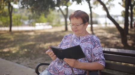 roman : Elderly woman with glasses in the Park on a bench reading an electronic book