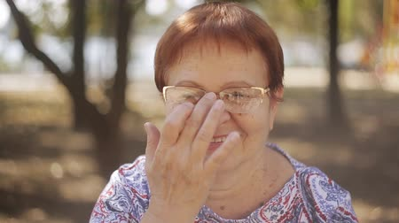 donna senior : portrait of happy elderly woman in park laughing enjoying retired lifestyle wearing glasses