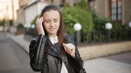 beatiful : Portrait of a girl in a leather jacket with a backpack standing on the street in the background of his new home. Stock Footage