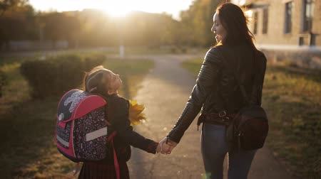 learning to walk : Mother and daughter return from school at sunset. Mother and daughter with a briefcase on the back going home from school, rear view Stock Footage