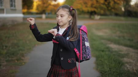 after school : Little girl with a big backpack shows her mother dance in the street near the school. Stock Footage