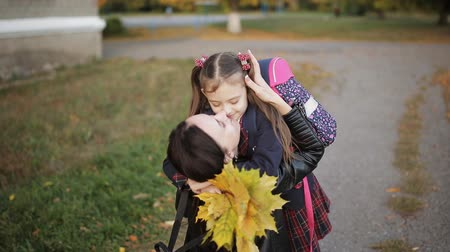 pozdrav : The little girl runs home from school to moms embrace. Mother meets daughter from school