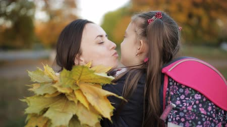 pozdrav : Mother and daughter hugging with a bouquet of autumn leaves. The meeting of mother and daughter after school. Dostupné videozáznamy