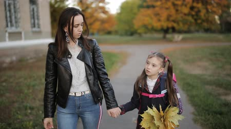 learning to walk : Mother and a little girl with a backpack on shoulders and a bouquet of yellow autumn leaves in hand back home from school. Mother and daughter walking hand in hand from school after school.