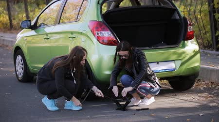 spare : Emergency. Two women at the roadside trying to change a tire from your car with a Jack. Stock Footage