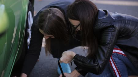 országúti : Closeup of two young woman lifting broken car with jack screw on the side of the road.