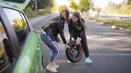 replace : Two women taking out spare wheel out of the car and rolling it on ground
