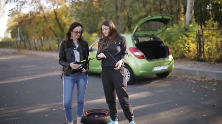 привлекать : The two women dancing near the car with a broken wheel with the Jack and the hands.