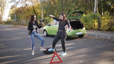 lastik : Two women at the roadside dancing near the car with a broken wheel, attracting the attention of drivers. Stok Video