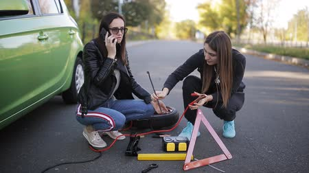 desamparado : The problem on the road. The breakdown of a car. Call technical assistance. Two women near a broken car.