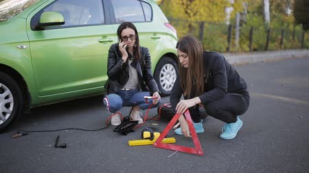 sos : Two women call for help on the phone on the side of the road next to broken car Stok Video