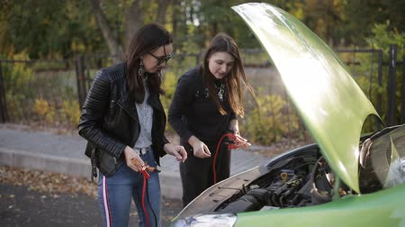 clamp : Two not too bright girls trying to recharge a dead car battery. Two girls at the open hood of a car trying to connect to the battery leads for charging