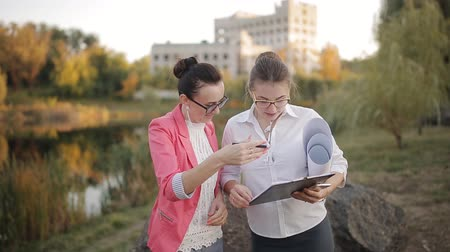 working together : Two women agree on the documentation for the procurement of construction materials for completion of the construction of the building. Stock Footage