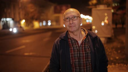 отцовство : An elderly man against night shined city. City lights background