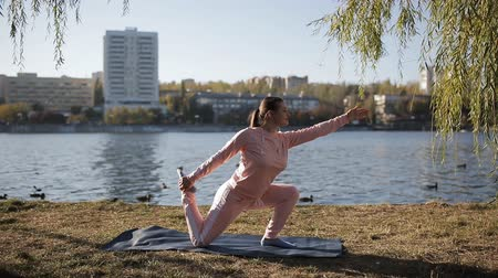 jimnastik : Beautiful girl in a tracksuit on the citys waterfront does yoga. Stok Video