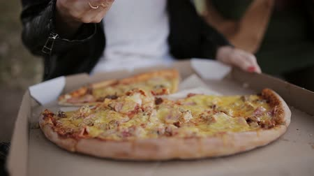 peperoni : Close-up Of People Hands Taking Slices Pizza. Frame. Takes eating a slice of pizza with cheese, tomatoes and ham. Delicious food for gluttony and enjoyment. Stock Footage
