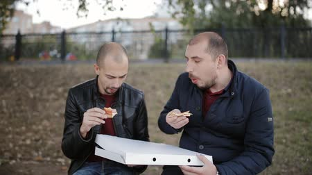 mastication : Two men friends sitting on a bench in the Park and eating pizza out of the box