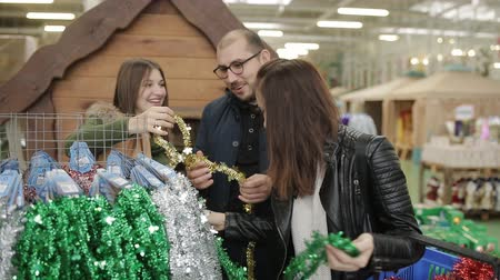 seçme : Friends in the supermarket at the Christmas sale choose colorful tinsel to decorate the Christmas tree.