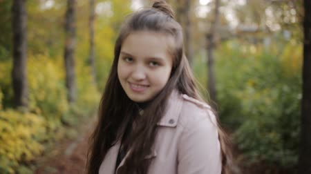 aparat ortodontyczny : Girl teenager plays with her hair looking at camera in autumn Park.