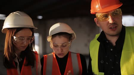 bouwwerf : The engineer communicates with the female customer representatives at the construction site, checking the drawings with the actual progress of construction work Stockvideo