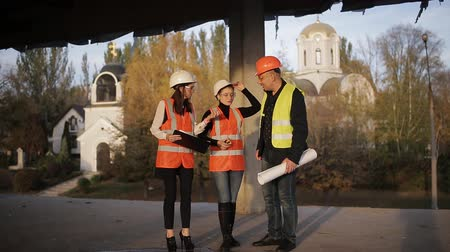 kolumny : Foreman shows two women inspectors to the construction site.