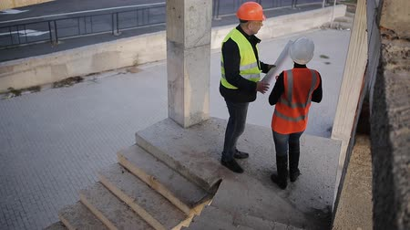 yönetici : Expert engineers and construction supervisor lift up the stairs of construction site. Stok Video