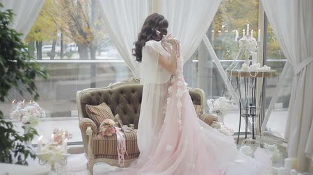 negligee : young beautiful bride in lingerie is spinning in dance with her wedding dress Stock Footage