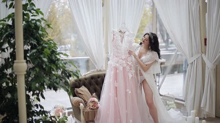 negligee : Young beautiful girl in the hands holds a wedding dress. Happy bride in a room with large windows and with candles in candelabra.