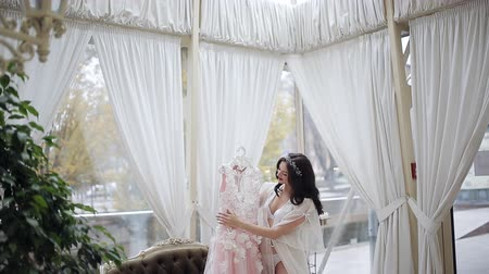 nevěsta : A young girl in a large and bright room is preparing to wear a wedding dress. Happy bride in penayur stands holding wedding dress Dostupné videozáznamy