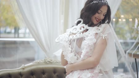 negligee : A young girl in a large and bright room is preparing to wear a wedding dress. Happy bride in penayur stands holding wedding dress Stock Footage