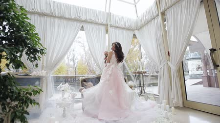 negligee : A happy bride in a wedding dress whirls in dance with her wedding bouquet. Young girl in a beautiful pink dress. Stock Footage