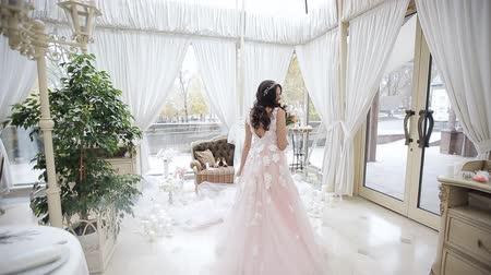negligee : A young girl in a beautiful pink dress in a large and bright room, there are a lot of candles and delicate decor. A happy bride in a wedding dress whirls in dance with her wedding bouquet Stock Footage