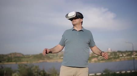 goggles : A middle-aged man uses virtual reality glasses in the nature